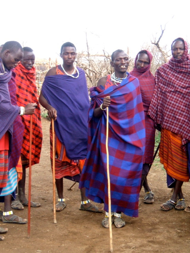 Masai men stand in a group after dancing.